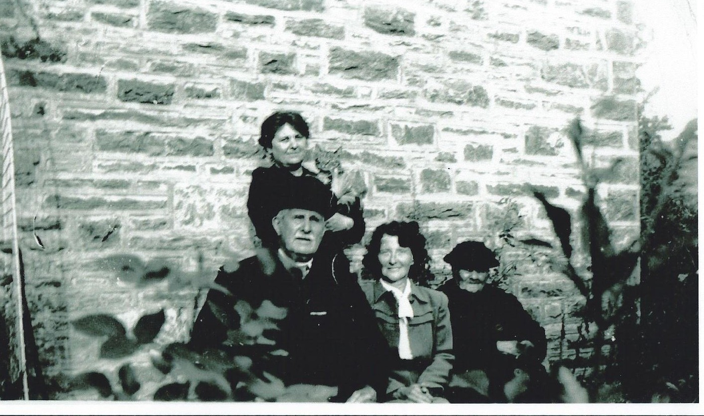 Mary Ann Daniels holds the family tabby in 1940.  Seated in front are her parents and their evacuee guest