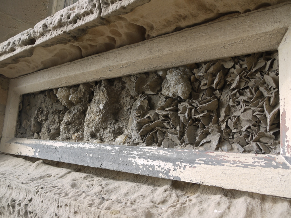 A geological panel below a window on the Queen's Hotel