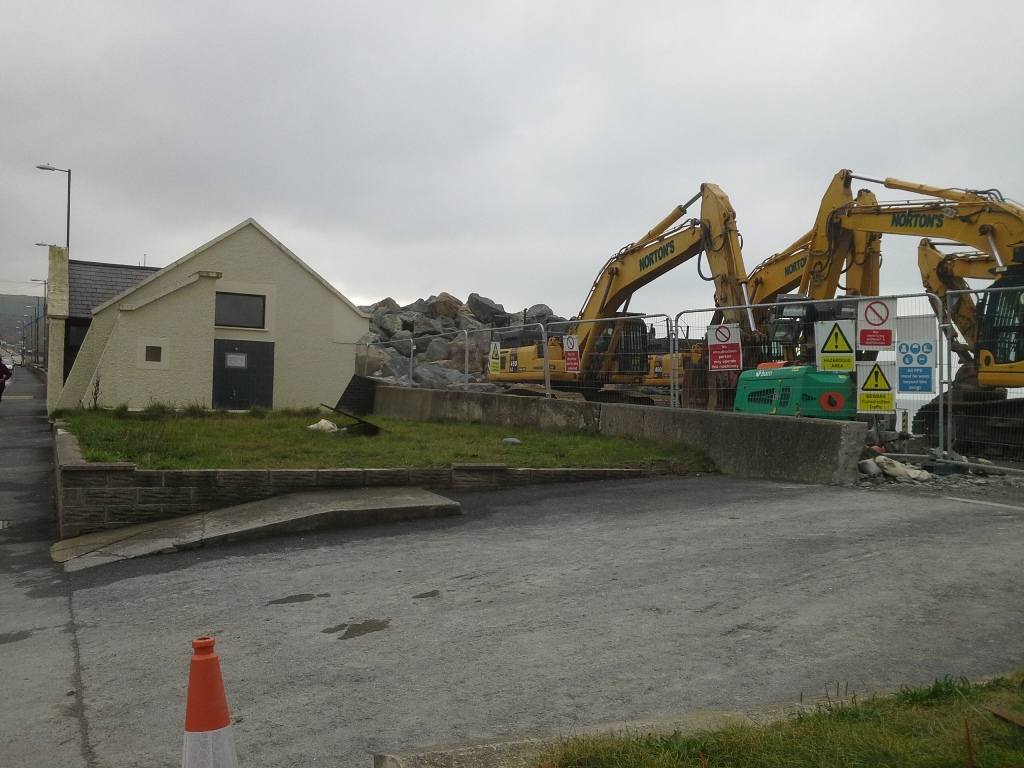 Diggers parked by the Public Conveniences on Borth sea front.  A huge stone pile awaits its final location on the lower shore.